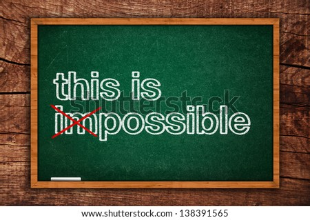 This is possible message written on green chalkboard, motivational positive thinking concept of possible and impossible - stock photo