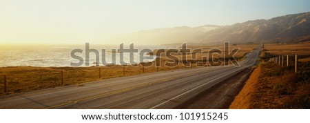 This is Route 1, also known as the Pacific Coast Highway. The road is situated next to the ocean with the mountains in the distance. - stock photo