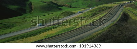 This is Route 580 at the Altamont Pass. There is green grass on each side of the highway with two separate roads for cars to travel in each direction. - stock photo