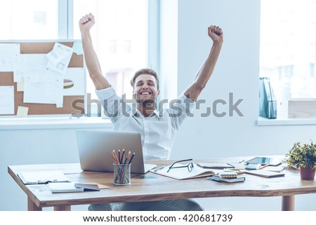 This is success! Cheerful young handsome man keeping arms outstretched and keeping eyes closed with smile while sitting at his working place - stock photo