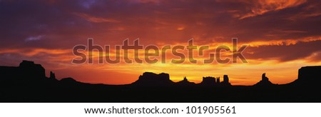 This is sunrise on Monument Valley. The rocks are in silhouette against an orange sky. - stock photo