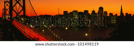 This is the Bay Bridge and skyline at sunset. There is an orange glow in the sky. - stock photo