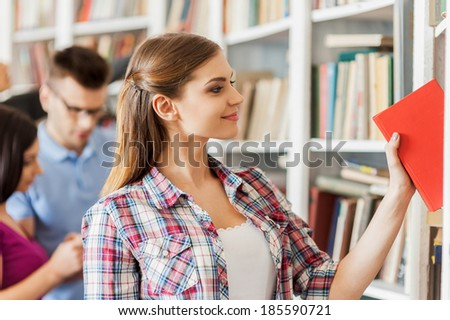 This is the book I need. Beautiful young woman picking a book from the bookshelf while people standing behind her - stock photo