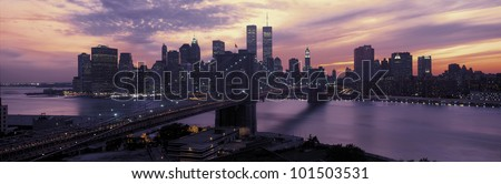This is the Brooklyn Bridge over the East River and the Manhattan skyline at sunset. There is a purple cast to the sky and the lights to the buildings are starting to come on. - stock photo
