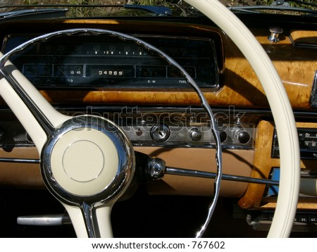 This is the dashboard of an older model Mercedes convertible - the 220s to be exact.  This roadster is sleek and shiny. - stock photo