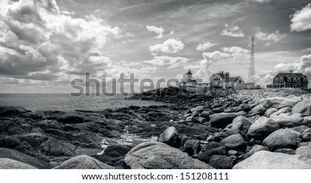 This is the Eastern Point Lighthouse sitting on a point of land extending from Gloucester Harbor in Massachusetts. - stock photo