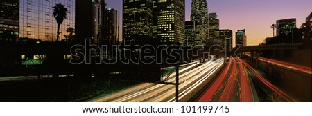This is the Harbor Freeway with rush hour traffic at sunset. The yellow and red streaked lights from the cars are on the freeway. - stock photo