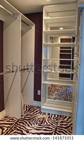 This is the inside of a beautiful empty closet, with shelves and mirrors, hanging clothes racks, well lit.  It also has a zebra print carpet to an elegant home decor appeal.