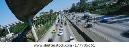 This is the Interstate 405 and 10 at rush hour. There are many cars lined up on the freeway with an overpass on the left hand side. There are a few houses to the right of the freeway. - stock photo