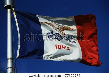 This is the Iowa State flag, waving in the wind. It is on a flagpole against a blue sky. There are three colors on the flag, the center background is white. - stock photo