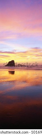 This is the Oregon coast at sunset. The large rock to the left is referred to as one of the sea stacks on the beach. The pink and blue sunset sky is reflected in the water on the beach. - stock photo