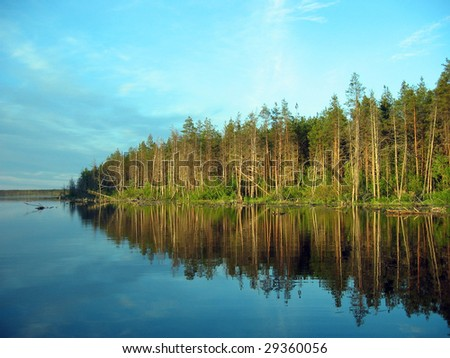 This is the picture of the quiet Karelian lake and the distant forest under the light of the rising sun