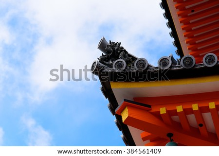 This is the roof edge of a Japanese shrine which is decorated by sculptures and patterns. - stock photo