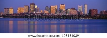 This is the State Capitol and skyline along the Charles River. It is the view from Harvard Bridge at sunset. - stock photo