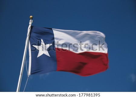 This is the State Flag flying in the wind. it is on a flagpole against a blue sky. There is a single white star on the left hand side against blue with a white stripe. - stock photo