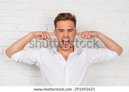 This is too loud! Frustrated man holding fingers in his ears  - stock photo