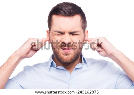 This is too loud! Frustrated mature man in shirt holding fingers in his ears and keeping eyes closed while standing against white background - stock photo