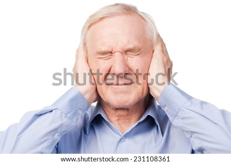 This is too loud! Frustrated senior man in shirt holding head in hands and keeping eyes closed while standing against white background - stock photo
