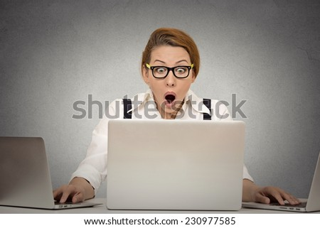 This is too much! Young woman can't handle workload anymore. Busy multitasking trying to manage it all by herself working on several computers simultaneously sitting at desk in office. Face expression - stock photo
