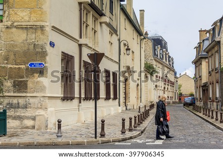 This is unknown woman crossing the road in the historic center May 15, 2015 in Reims, France.