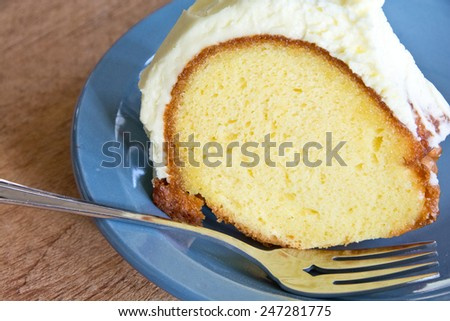This lemon cake has been frosted with lemon creme frosting and served on a blue plate.