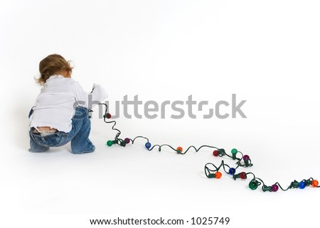 This little girl is surely up to no good playing with those christmas lights. - stock photo