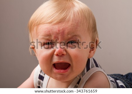 This little guy doesn't like something and wants to cry - stock photo