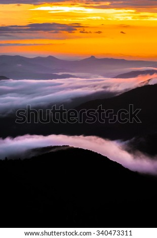 This magical and breathtaking sunrise was taken in the Blue Ridge Mountains of North Carolina after a night of camping and hiking.  - stock photo