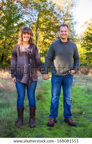 This man and woman heterosexual couple is together outdoors posing for a portrait.