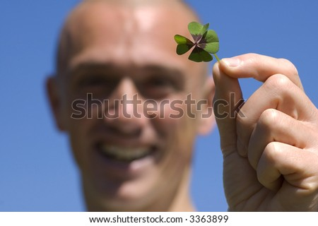 This man found a four leaf clover, it's his lucky day! - stock photo