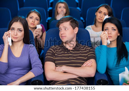 This movie is for ladies only. Young man sitting together with crying women while watching movie at the cinema - stock photo
