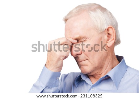 This pain torturing me! Frustrated senior man in shirt holding hand on his head and keeping eyes closed while standing against white background - stock photo