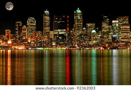 This photo is of Seattle Washington's business district at night with a full moon and gorgeous cityscape lights reflecting off the water of Puget Sound.  No space needle in this photo. - stock photo
