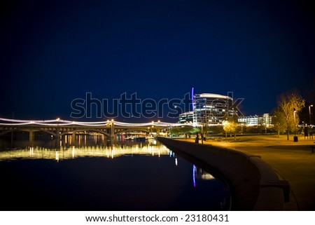 This photo is showcasing the landmark Mill Ave Bridge in Tempe Arizona. Shown here crossing the Tempe Town Lake in a night setting. - stock photo