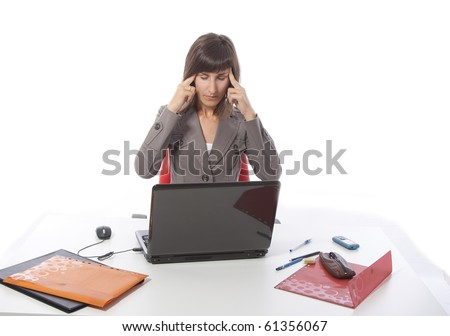 This photo shows a business woman talking on the phone and working on the computer.