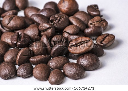 This photo shows a closeup of some coffee beans on a white background.