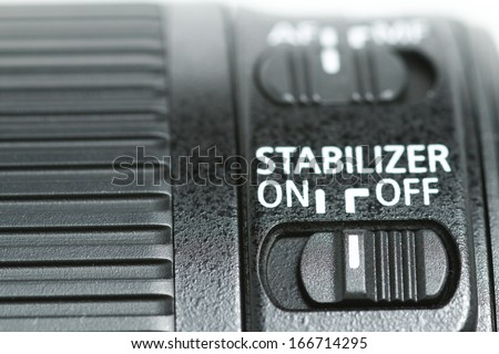 "This photo shows a closeup to a lens stabilizer button on the ""Off"" position ."