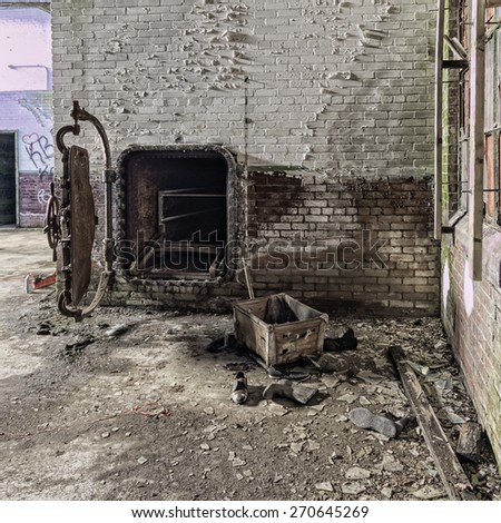 This photo was taken looking inside the laundry building of the former Foxboro State Hospital.   This looks more like a crematorium than a cloths drier.