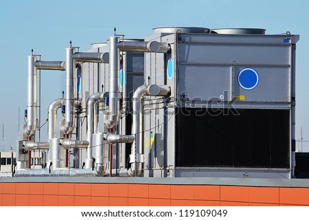 This photograph represents an industrial air conditioning unit cooling system on the roof of a building - stock photo