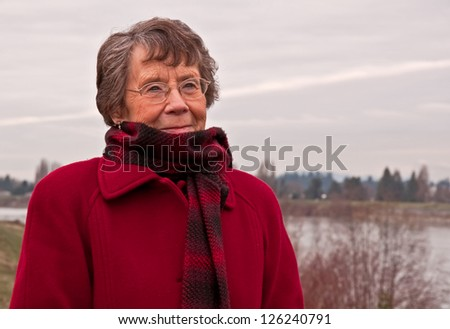 This portrait of a Caucasian senior citizen lady as she stands outside in the cold.  She's wearing a red, wool coat and plaid red scarf.  A river is in the background. - stock photo