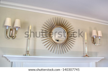 This scene is a light colored fireplace mantle scene of an interior design.  A couple of wall sconce lights and a mirror complete the clean, simple lines of this room. - stock photo