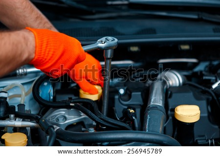 This seem to be a problem. Cropped image of handsome car mechanics with a spanner checking the engine under hood in the car service station - stock photo