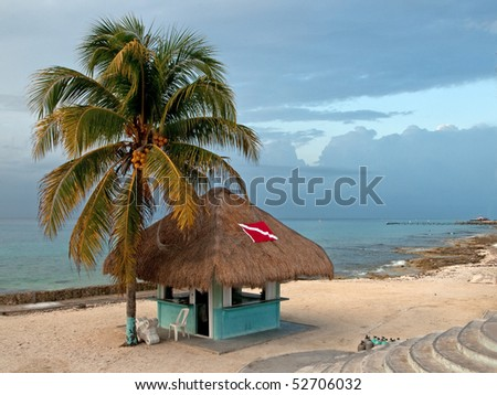 This shot of a beach-side dive shack was taken in Cozumel, Mexico, at dusk. - stock photo
