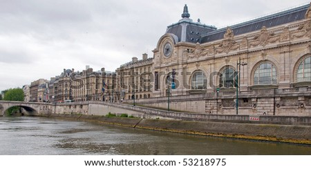 This shot of the Musee d'Orsay was taken from the middle of the Seine River in Paris on an overcast day. - stock photo