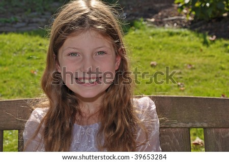 This smiling happy 9 year old Caucasian girl is sitting outside on a wooden bench. - stock photo