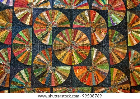 This stock image is a black colorful quilt in many round shapes for a unique abstract pattern and texture design.  Beautiful fabric artwork. - stock photo