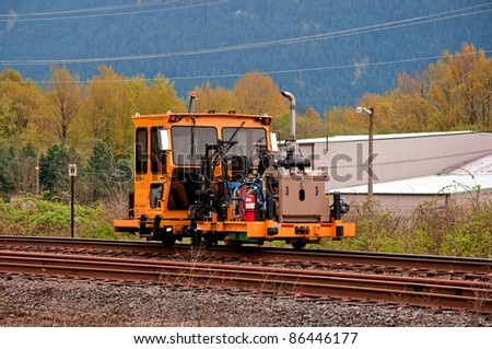 This stock image shows a single machinery equipment with an unidentified person working on railroad tracks.  Photos taken in early spring with mountains in the background. - stock photo