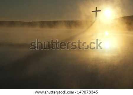 This Sunrise Cross on a misty lake casts a lengthy shadow and reflection on this calm Easter Morning Illustration - stock photo