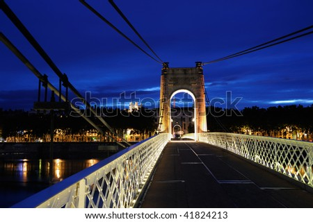 This Suspension bridge gravity-anchored (Passerelle du college, over Rhone) was completed in 1844, destroyed in 1944 and later rebuilt identically. - stock photo