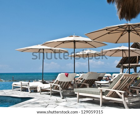 This tropical image is a luxury paradise with chaise lounges and umbrellas overlooking the turquoise tropical ocean, beckoning to come and relax. - stock photo